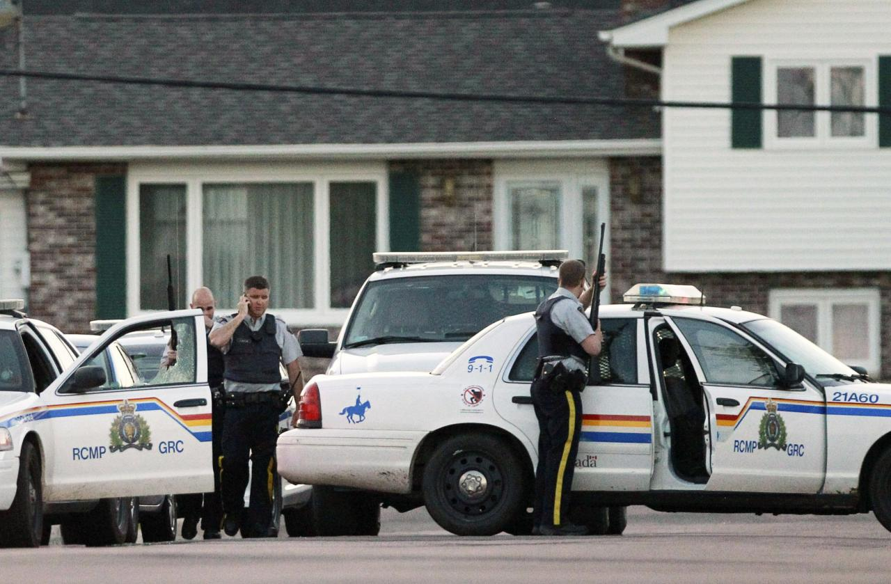 Codiac RCMP officers take cover behind their vehicle in Moncton, New Brunswick June 4, 2014. Three police officers were shot dead and two more were wounded, police said as they conducted a manhunt for a man carrying a rifle and wearing camouflage clothes. Police said they were searching for Justin Bourque, 24, of Moncton. REUTERS/Viktor Pivarov/Moncton Times & Transcript (CANADA - Tags: CRIME LAW) FOR EDITORIAL USE ONLY. NOT FOR SALE FOR MARKETING OR ADVERTISING CAMPAIGNS. NO ARCHIVES. NO SALES