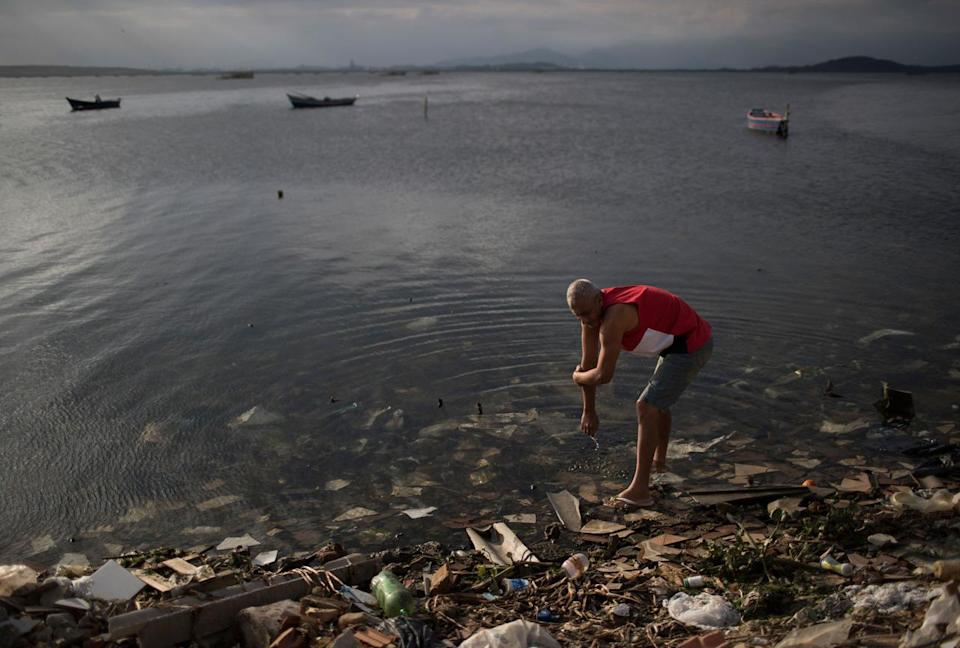 """<p>A man washes himself in the polluted waters of Guanabara Bay in Rio de Janeiro, Brazil, Saturday, July 30, 2016. While local authorities including Rio Mayor Eduardo Paes have acknowledged the failure of the city's water cleanup efforts, calling it a """"lost chance"""" and a """"shame,"""" Olympic officials continue to insist Rio's waterways will be safe for athletes and visitors. (AP Photo/Felipe Dana)</p>"""