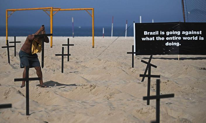 """<span class=""""element-image__caption"""">Marcio Antonio Silva, whose son died of coronavirus, re-erects crosses built by activists symbolizing deaths from Covid-19 after a Bolsonaro supporter vandalized the memorial.</span> <span class=""""element-image__credit"""">Photograph: Carl de Souza/AFP/Getty Images</span>"""