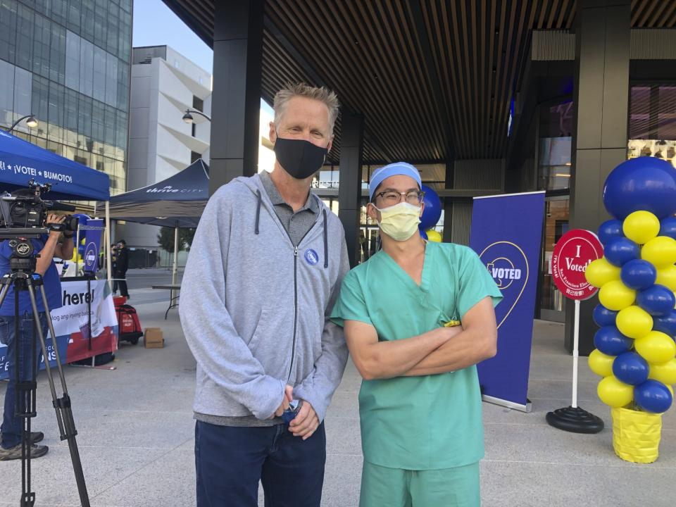 Golden State Warriors coach Steve Kerr poses with pharmacy technician Charles Dee by a ballot drop-off location at Chase Center on Saturday, Oct. 31, 2020, in San Francisco. (AP Photo/Janie McCauley)