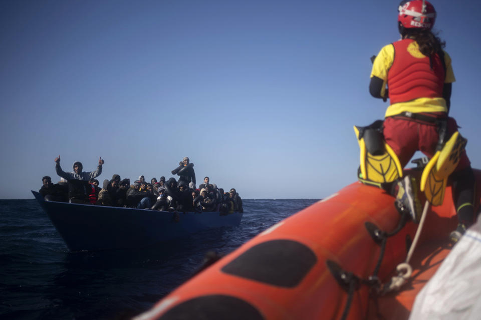 Migrants from Eritrea, Egypt, Syria and Sudan, are assisted by aid workers of the Spanish NGO Open Arms, after fleeing Libya on board a precarious wooden boat in the Mediterranean sea, about 110 miles north of Libya, on Saturday, Jan. 2, 2021. (AP Photo/Joan Mateu)