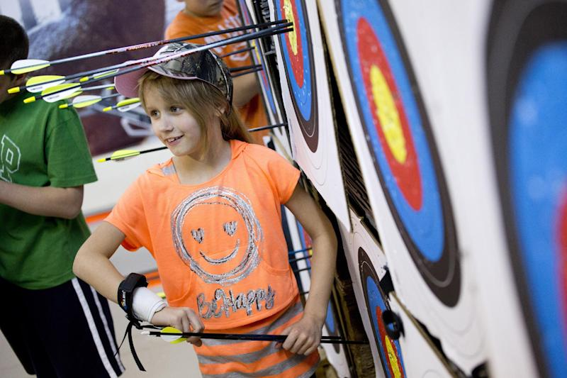"""In this April 13, 2012 photo, Christa Mattessich of Oakland, N.J., 7, retrieves her arrows after a round in the youth archery league at Targeteers Archery in Saddle Brook, N.J. In schools and backyards, for their birthdays and out with their dads, kids are gaga for archery a month after the release of """"The Hunger Games."""" Archery ranges around the country have enjoyed a steady uptick among kids of both sexes in the movie's lead-up, though 16-year-old heroine Katniss Everdeen, the archery ace seems to resonate with girls more than boys. (AP Photo/Charles Sykes)"""