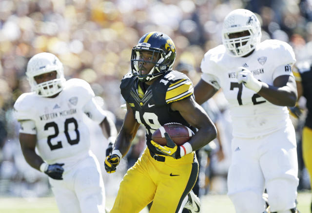 Iowa defensive back B.J. Lowery, center, runs from Western Michigan's Brian Fields, left, and Taylor Moton, right, while returning an interception 35-yards for a touchdown during the first half of an NCAA college football game, Saturday, Sept. 21, 2013, in Iowa City, Iowa. (AP Photo/Charlie Neibergall)