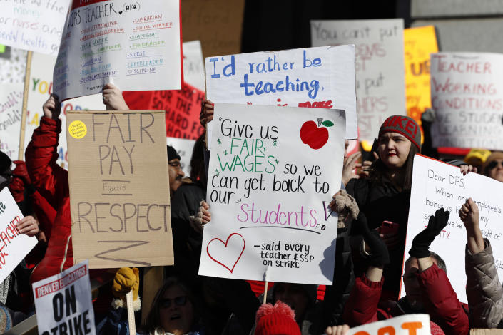 Teachers wave placards during a strike rally on the west steps of the State Capitol Monday, Feb. 11, 2019, in Denver. The strike is the first for teachers in Denver since 1994 and centers on base pay. (AP Photo/David Zalubowski)