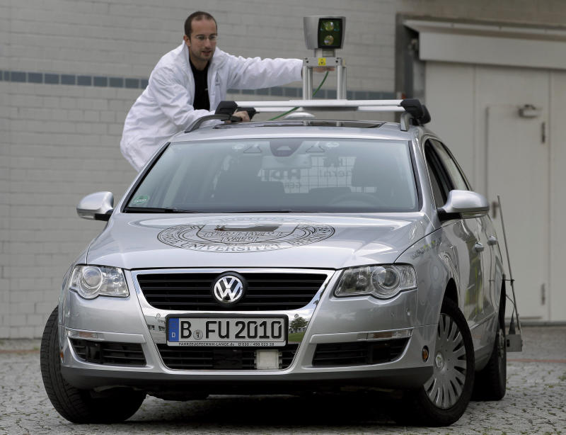 In this Friday, Sept. 16, 2011 photo Autonomos Labs assistant Paul Czerwionka touches a 360 degree laser scanner on top of a car Berlin, Germany. The car is driven by a computer that steers, starts and stops itself. The 360 degrees laser scanner on top of the car, a GPS system and other sensors monitor the surrounding traffic. A driver sits only for security reasons behind the steering wheel. The Autonomos team is part of the Artificial Intelligence Group of the Free University Berlin (AP Photo/Michael Sohn)