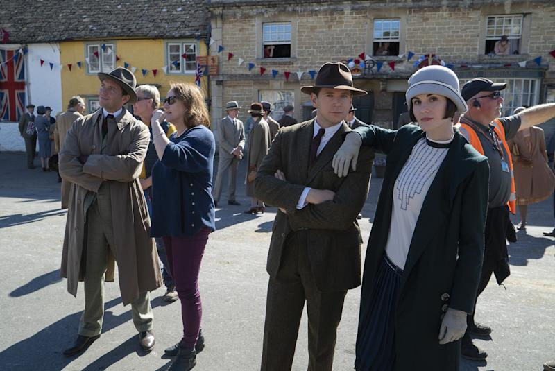 allen leech and michelle dockery dressed in 1920s attire on a concrete movie set of the new downton abbey movie