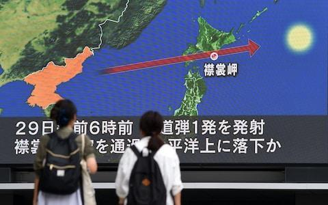 <span>Pedestrians watch the news on a huge screen displaying the trajectory of the missile that flew over Japan</span> <span>Credit: AFP </span>