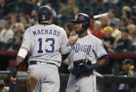 San Diego Padres' Manuel Margot, right, and Manny Machado (13) celebrate after they scored against the Arizona Diamondbacks during the first inning of a baseball game Saturday, April 13, 2019, in Phoenix. (AP Photo/Ross D. Franklin)