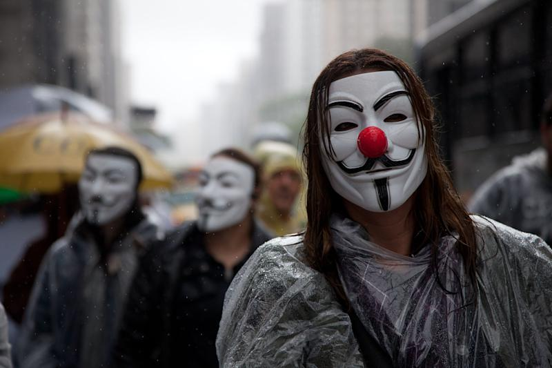 Demonstrators walk on Av.Paulista wearing Guy Fawkes or V for Vendetta masks during the demonstration against corruption in Sao Paulo, Brazil on November 15, 2011. AFP PHOTO/YASUYOSHI CHIBA (Photo by Yasuyoshi CHIBA / AFP) (Photo credit should read YASUYOSHI CHIBA/AFP via Getty Images)