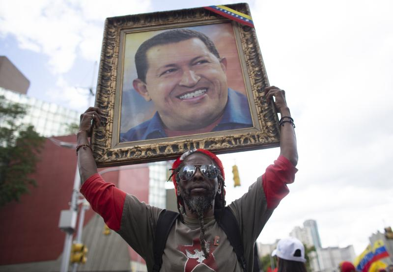 A supporter of President Nicolas Maduro holds up a painting of late President Hugo Chavez during an anti-imperialist rally in Caracas, Venezuela, Saturday, August 31, 2019. Venezuelan officials say they have proof of paramilitary training camps operating in neighboring Colombia where groups are purportedly plotting attacks to undermine President Nicolás Maduro. (AP Photo/Ariana Cubillos)