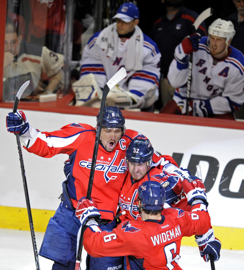 Washington Capitals defenseman Mike Green, center, celebrates his goal with teammates Alex Ovechkin (8), of Russia, and Dennis Wideman (6)  during the third period of Game 4 of an NHL hockey Stanley Cup second-round playoff series against the New York Rangers Saturday, May 5, 2012, in Washington. The Capitals won 3-2 to even the best-of-seven games series 2-2. (AP Photo/Nick Wass)