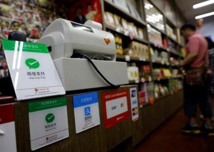 FILE PHOTO: Signs accepting WeChat Pay and AliPay are displayed at a shop in Singapore May 22, 2018. Picture taken May 22, 2018. REUTERS/Edgar Su/File Photo