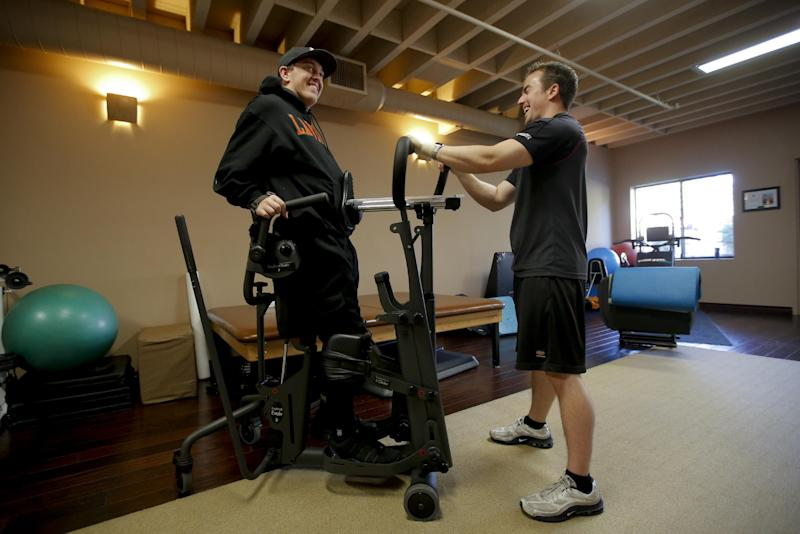 Hal Hargrave Jr., left, who is paralyzed from the neck down after a car crash when he was 17, shares a laugh with his trainer Chris Fitzgerald during his physical therapy session at a gym in Claremont, Calif., Wednesday, Dec. 19, 2012. After years of grueling physical therapy, Hargrave started the nonprofit Be Perfect Foundation and raised $2 million to help other young people who couldn't afford the same kind of rehabilitation program made available to him. (AP Photo/Jae C. Hong)
