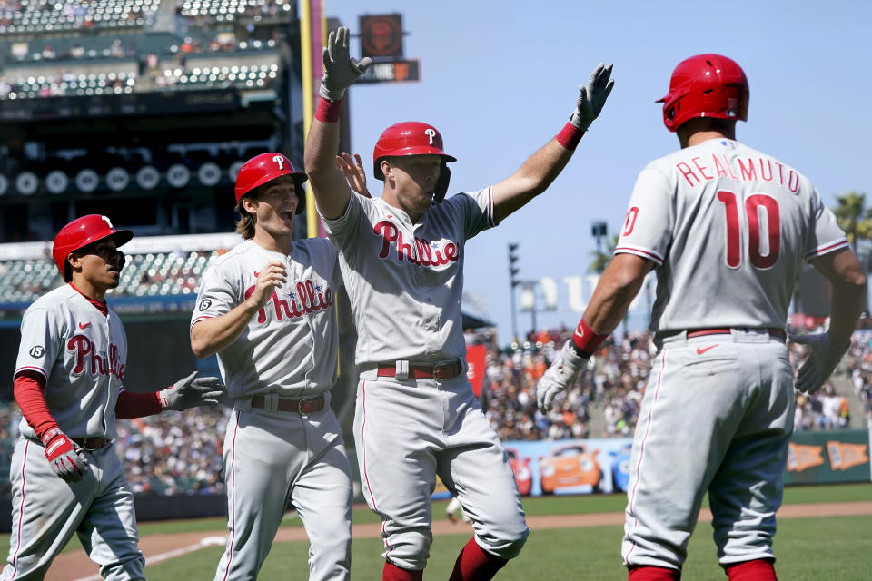 Philadelphia Phillies' Rhys Hoskins, second from right, celebrates after hitting a three-run home run that also scored Ronald Torreyes, left, and Luke Williams, second from left, during the seventh inning of a baseball game against the San Francisco Giants in San Francisco, Saturday, June 19, 2021. Phillies' J.T. Realmuto, right, looks on. (AP Photo/Jeff Chiu)