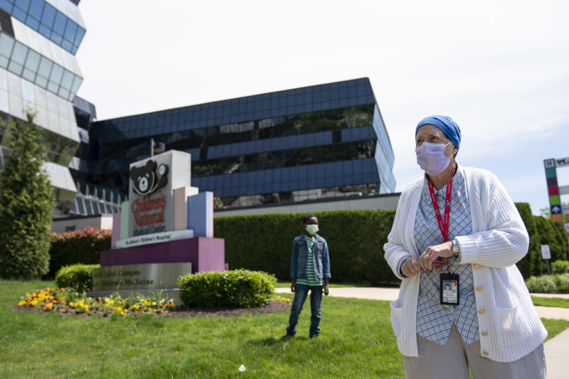 Registered nurse Jean Boone watches from Children's National Hospital as the U.S. Navy Blue Angels and U.S. Airforce Thunderbirds fly over the D.C. area on May 2, 2020 in Washington, DC. (Photo: Sarah Silbiger/Getty Images)