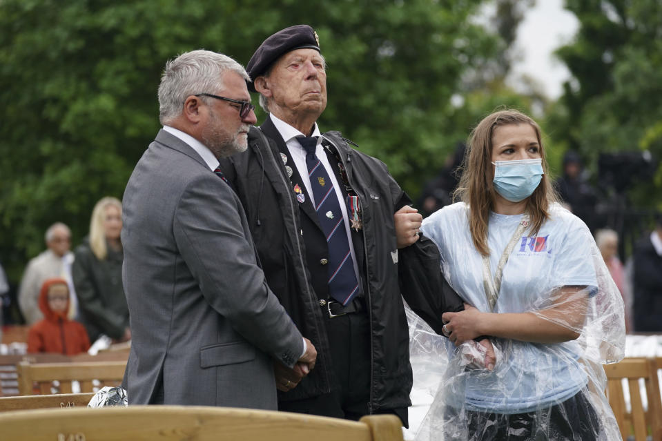 A veteran is assisted during the official opening of the British Normandy Memorial in France via a live feed, during a ceremony at the National Memorial Arboretum in Alrewas, England, Sunday, June 6, 2021. Several ceremonies are scheduled on Sunday to commemorate the 77th anniversary of D-Day that led to the liberation of France and Europe from the German occupation. On June 6, 1944, more than 150,000 Allied troops landed on code-named beaches, carried by 7,000 boats. (Jacob King/PA via AP)