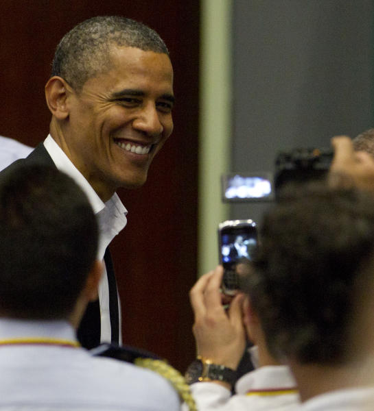 President Barack Obama smiles to people in the audience taking his picture during the arrival ceremony at the sixth Summit of the Americas in Cartagena, Colombia, Saturday April 14, 2012. (AP Photo/Carolyn Kaster)