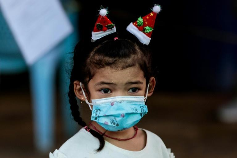 A girl wearing a face mask and Santa Claus hats watches as medical officials test people for coronavirus at the seafood market