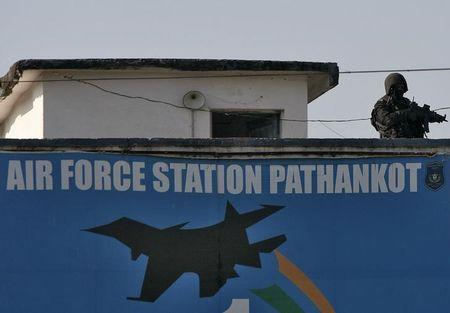 An Indian security personnel stands guard on a building at IAF base at Pathankot