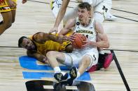 Michigan guard Franz Wagner (21) and Maryland forward Galin Smith (30) go to the floor for a loose ball in the first half of an NCAA college basketball game at the Big Ten Conference tournament in Indianapolis, Friday, March 12, 2021. (AP Photo/Michael Conroy)