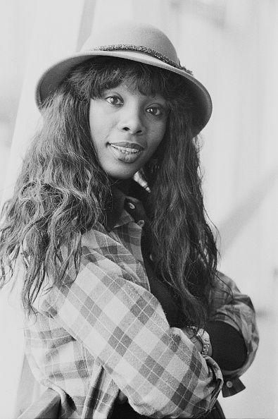 <p>Donna Summer tucks her long hair under a bowler hat, while her curly bangs peek out of the front. </p>