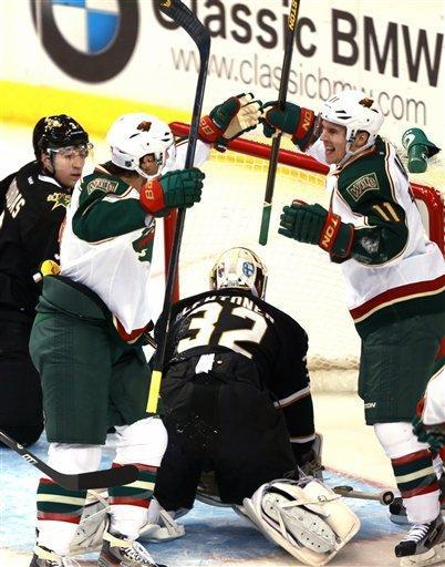 Minnesota Wild center Matt Cullen, left, and teammate Zach Parise (11) celebrate Parise's goal on Dallas Stars goalie Kari Lehtonen (32) during the first period of an NHL hockey game Monday, March 25, 2013 in Dallas. (AP Photo/ Michael Mulvey)