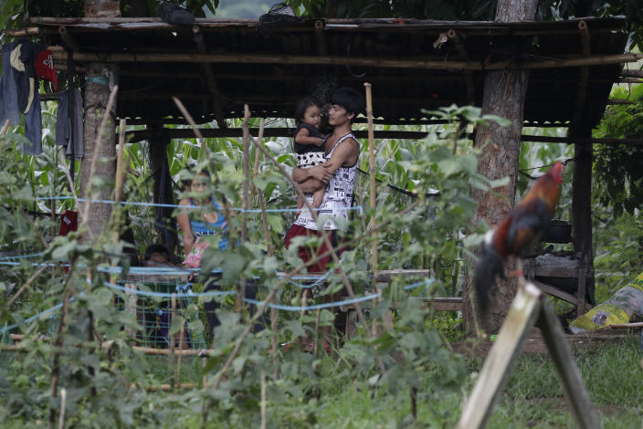 Ronnel Manjares, right, carries his daughter Crystal outside their house in Tanauan, Batangas province, Philippines, Wednesday, July 15, 2020. His 16-day-old son Kobe Christ Manjares was heralded as the country's youngest COVID-19 survivor. But the relief and joy proved didn't last. Three days later, Kobe died on June 4 from complications of Hirschsprung disease, a rare birth defect. (AP Photo/Aaron Favila)