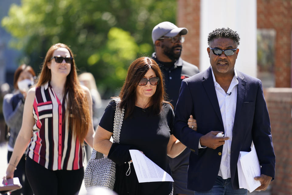 """FILE - Former NFL players Ken Jenkins, right, and Clarence Vaughn III, center right, along with their wives, Amy Lewis, center, and Brooke Vaughn, left, carry tens of thousands of petitions demanding equal treatment for everyone involved in the settlement of concussion claims against the NFL, to the federal courthouse in Philadelphia, in this Friday, May 14, 2021, file photo. The NFL on Wednesday, June 2, 2021, pledged to halt the use of """"race-norming"""" — which assumed Black players started out with lower cognitive functioning — in the $1 billion settlement of brain injury claims and review past scores for any potential race bias.(AP Photo/Matt Rourke, File)"""