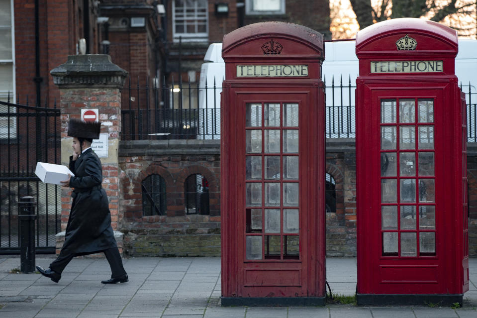 LONDON, ENGLAND - APRIL 08: A man walks past a pair of telephone boxes in Stamford Hill on the evening of the Jewish holiday of Passover on April 8, 2020 in London, England. The Jewish community is preparing to celebrate Passover amid COVID-19 home isolation and social distancing measures. (Photo by Hollie Adams/Getty Images)