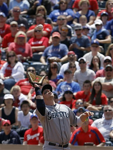 Seattle Mariners first baseman Justin Smoak (17) catches pop fly hit by Texas Rangers Ian Kinsler (5) in the first inning of an MLB American League baseball game at Rangers Ballpark in Arlington, Sunday, April 21, 2013, in Arlington, Texas. (AP Photo/Brandon Wade)