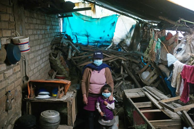 A woman and her child pose for a photograph inside their home in Chota