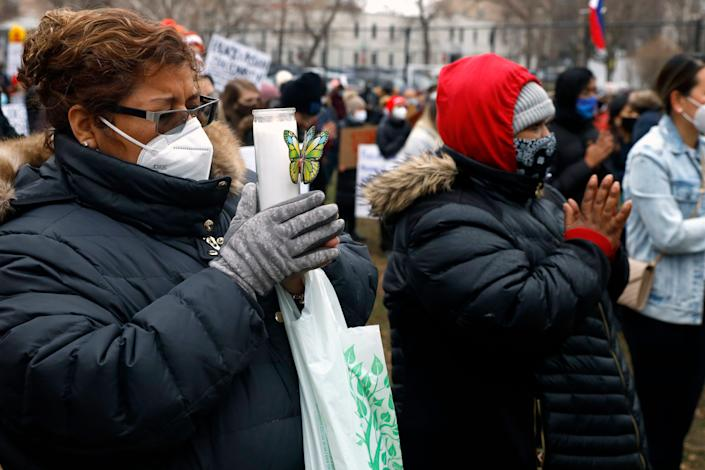 Two women remain in silence at a vigil and rally at Chicago's Horner Park on Friday, March 26, 2021, for the eight people killed in a shooting in Atlanta, Georgia. The event is organized by local Chicago organizations led by Asian Americans and Pacific Islanders. (AP Photo/Shafkat Anowar)