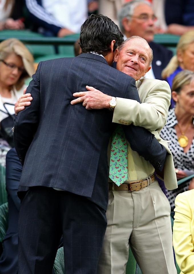 LONDON, ENGLAND - JUNE 28: England cricket captain Alastair Cook is hugged by Geoffrey Boycott as he takes his seat in the Royal Box on Centre Court on day five of the Wimbledon Lawn Tennis Championships at the All England Lawn Tennis and Croquet Club on June 28, 2013 in London, England. (Photo by Julian Finney/Getty Images)