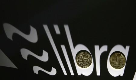 FILE PHOTO: Shadow of a 3D-printed Facebook Libra cryptocurrency logo is seen near cryptocurrency representation in this illustration taken
