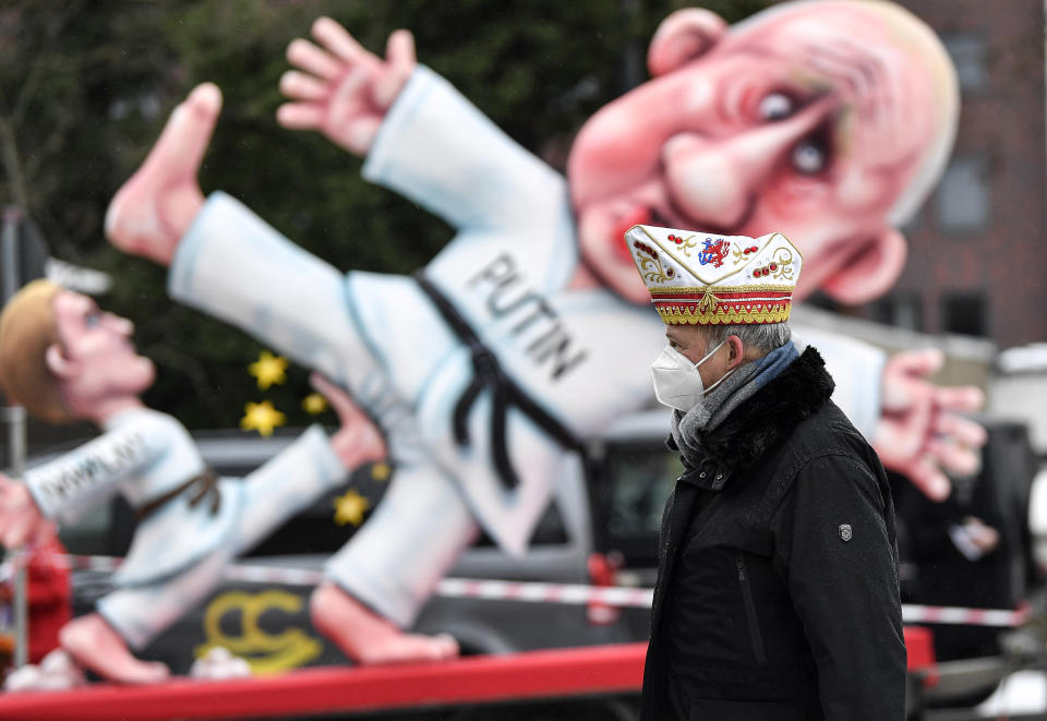 A reveller stands in front of a political carnival float depicting Russia's President Vladimir Putin fighting with opposition leader Alexei Navalny in the streets of Duesseldorf, Germany, Monday, Feb. 15, 2021. Because of the coronavirus pandemic the traditional 'Rosenmontag' carnival parade are canceled but eight floats are pulled through the empty streets in Duesseldorf, where normally hundreds of thousands of people would celebrate the street carnival. (AP Photo/Martin Meissner)