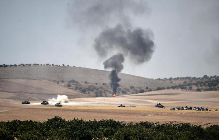 Turkish army tanks and pro-Ankara Syrian opposition fighter trucks pictured two kilometres west of the Syrian town of Jarabulus, in an image taken from the Turkish border city of Karkamis on August 24, 2016 (AFP Photo/Bulent Kilic)