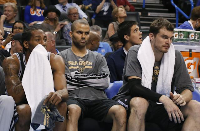San Antonio Spurs forward Kawhi Leonard, left, guard Tony Parker, center, and center Tiago Splitter watch from the bench in the fourth quarter of an NBA basketball game against the Oklahoma City Thunder in Oklahoma City, Thursday, April 3, 2014. Oklahoma City won 106-94. (AP Photo/Sue Ogrocki)