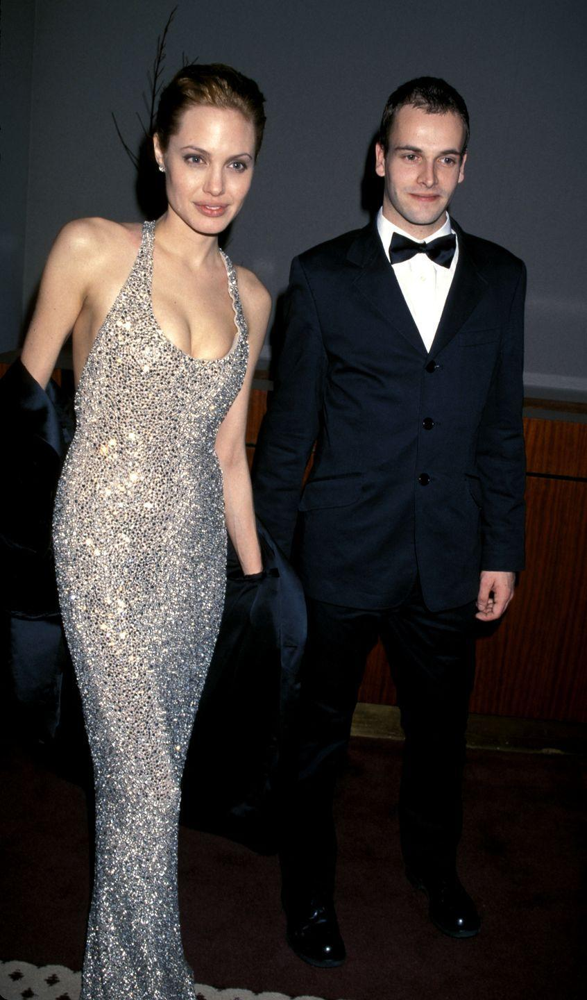 """<p>Angelina's marriage to Brad Pitt is well-documented, but it's often forgotten that her first husband was Jonny, who currently stars as Sherlock Holmes on the CBS procedural <em>Elementary</em>. After appearing in the 1995 movie<em> Hackers</em> together, they got hitched in 1996 with Angelina wearing black rubber pants and a white shirt with Jonny's name written in her own blood on the back. """"It's your husband,"""" she explained to the <em><a href=""""https://www.nytimes.com/1996/08/25/movies/following-ambivalently-in-mom-or-dad-s-footsteps.html?pagewanted=all"""" rel=""""nofollow noopener"""" target=""""_blank"""" data-ylk=""""slk:New York Times"""" class=""""link rapid-noclick-resp"""">New York Times</a> </em>that year. """"You're about to marry him. You can sacrifice a little to make it really special."""" They divorced in 2000, but in May 2014, Angelina <a href=""""https://www.usmagazine.com/celebrity-news/news/angelina-jolie-ex-husband-jonny-lee-miller-is-still-a-great-friend-2014285/"""" rel=""""nofollow noopener"""" target=""""_blank"""" data-ylk=""""slk:called him"""" class=""""link rapid-noclick-resp"""">called him</a> """"still a great friend.""""</p>"""