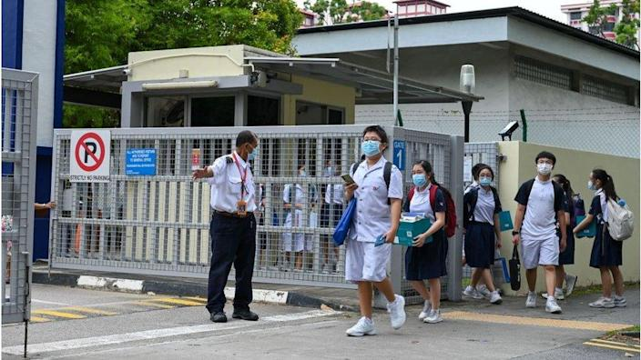 Students leave the River Valley High School compounds in Singapore on July 19, 2021, after a 13-year-old boy was found dead on the premises with multiple wounds, while a fellow student was arrested and an axe seized, police said.