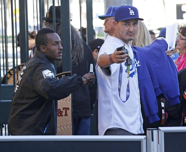 A security guard checks an arriving Los Angeles Dodgers fan before a baseball game between the San Francisco Giants and the Dodgers, Thursday, Sept. 26, 2013, in San Francisco. (AP Photo/George Nikitin)
