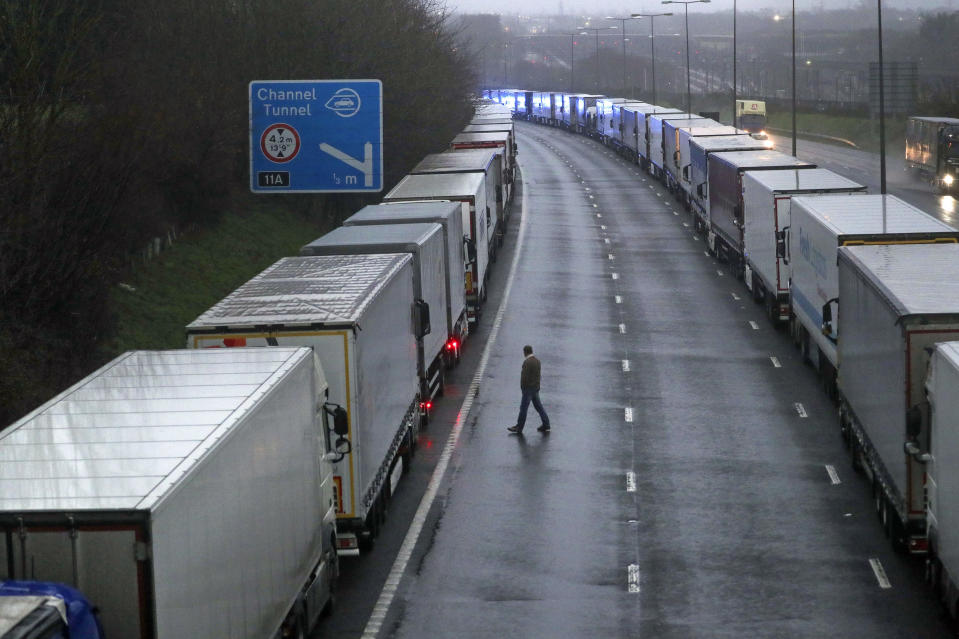 Lorries are parked on the M20 near Folkestone, Kent, England as part of Operation Stack after the Port of Dover was closed and access to the Eurotunnel terminal suspended following the French government's announcement, Monday, Dec. 21, 2020. France banned all travel from the UK for 48 hours from midnight Sunday, including trucks carrying freight through the tunnel under the English Channel or from the port of Dover on England's south coast. (Steve Parsons/PA via AP)