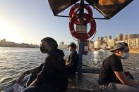 From left to right, Eric Roman, vocalist, Jeff Zacarias, AJ, president of the Dubai Filipino performers' union and Rommel Cuison, guitarist cross the creek water on a boat in Dubai, United Arab Emirates, Wednesday, Oct. 28, 2020. As the coronavirus pandemic mutes Dubai's live-music scene, the Filipino show bands that long have animated the city's storied nightlife are being disproportionately squeezed. Many are out of work and out of money, struggling to survive in overcrowded dormitories at the mercy of employers (AP Photo/Kamran Jebreili)