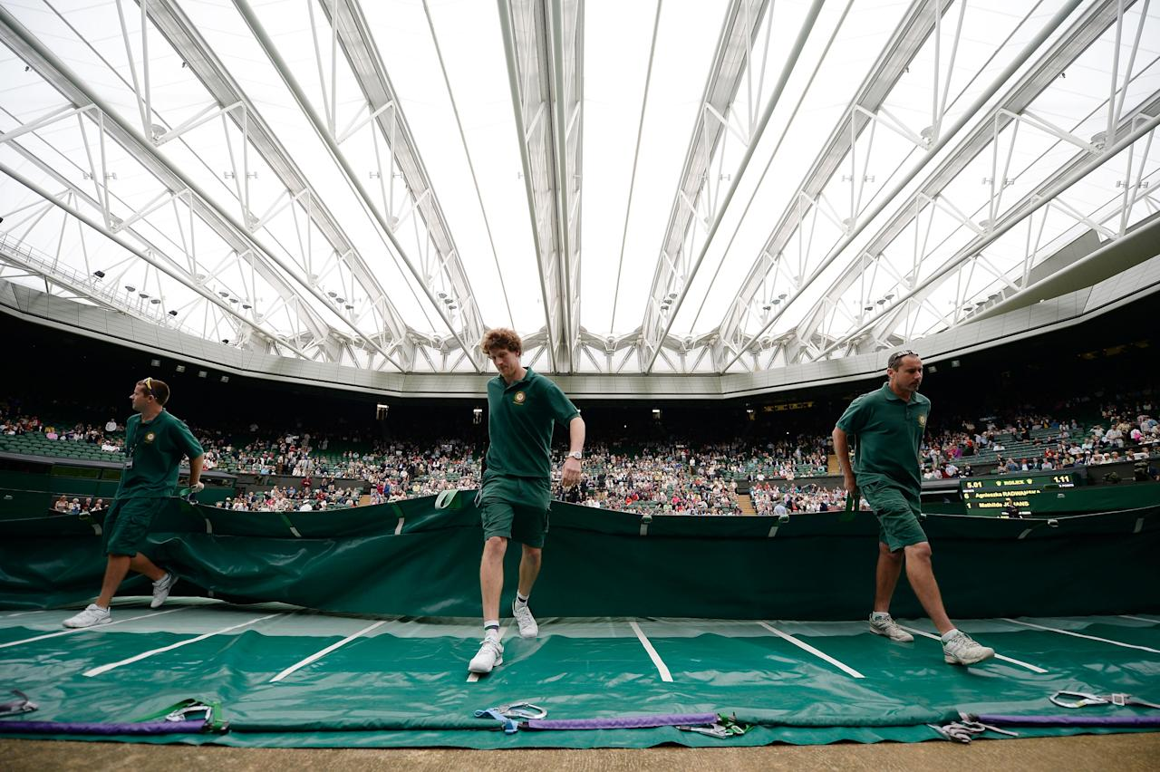 LONDON, ENGLAND - JUNE 27: Ground staff pull the rain covers off Centre Court under a closed roof after rain interrupted play during the Ladies' Singles second round match between Agnieszka Radwanska of Poland and Mathilde Johansson of France on day four of the Wimbledon Lawn Tennis Championships at the All England Lawn Tennis and Croquet Club on June 27, 2013 in London, England. (Photo by Dennis Grombkowski/Getty Images)