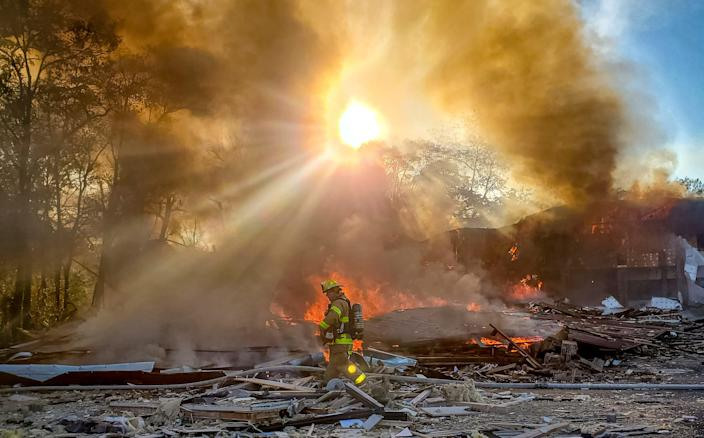 A firefighter walks through the burning rubble of a shopping center after an explosion in Harrisonburg, Va., on , Oct. 17, 2020.