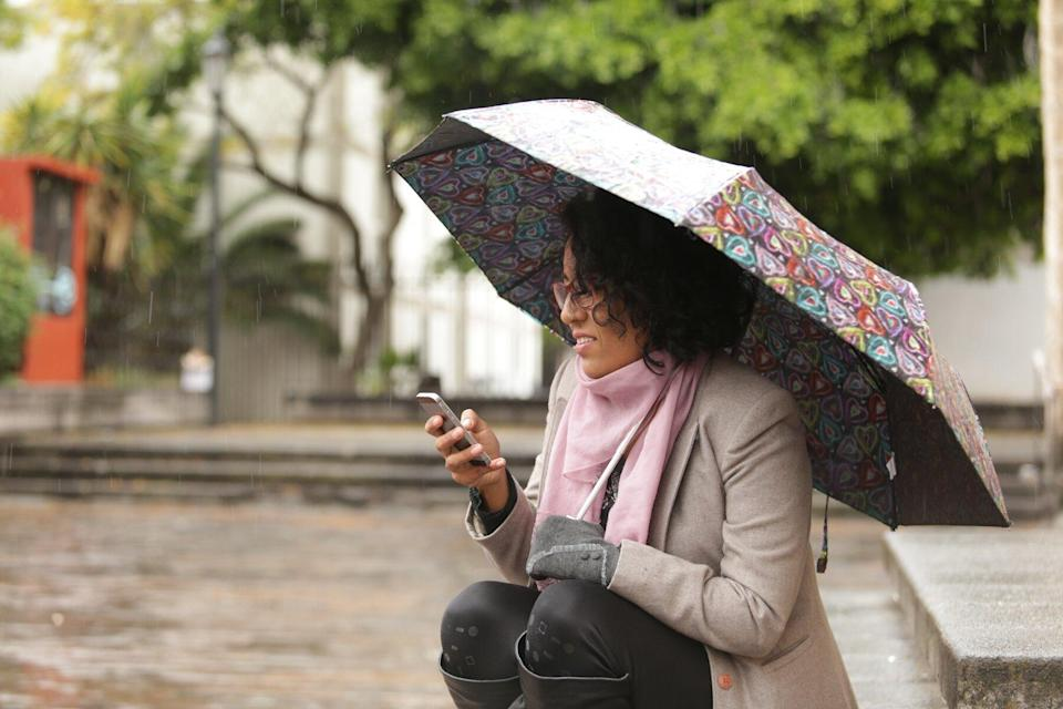 woman with umbrella using mobile phone