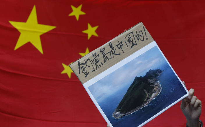"""A protester demonstrating against Japan's claim to disputed islands holds a picture of the rocky islands, known as Senkaku to Japanese and Diaoyu to Chinese, reading """"Diaoyu belongs to China"""" in front of a Chinese national flag during a rally outside the Japanese Consulate General in Hong Kong, Tuesday, Sept. 11, 2012. A territorial flare-up between China and Japan intensified Tuesday as Beijing sent patrol ships near the disputed East China Sea islands in a show of anger over Tokyo's purchase of the largely barren outcroppings from their private owners. (AP Photo/Kin Cheung)"""
