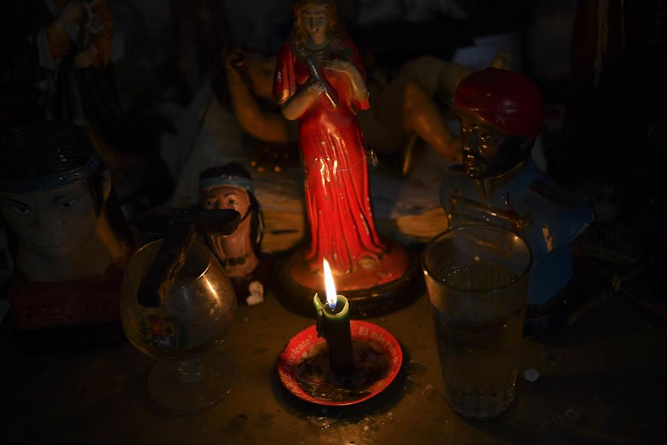 "A lit candle is seen on an altar with a diversity of saints, as well as the image of late Venezuelan president Hugo Chavez, at the clinic of healer ""Brother Guayanez"" in the emblematic neighborhood of Petare in Caracas, Venezuela on January 18, 2019. - Venezuela marked on February 2, 2019 20 years since President Nicolas Maduro's predecessor Hugo Chavez came to power. Chavez, who was first elected in 1999, mixed a larger-than-life personality with a man-of-the-people style, his popularity underpinned by oil-funded social programs. (Photo by YURI CORTEZ / AFP)        (Photo credit should read YURI CORTEZ/AFP/Getty Images)"
