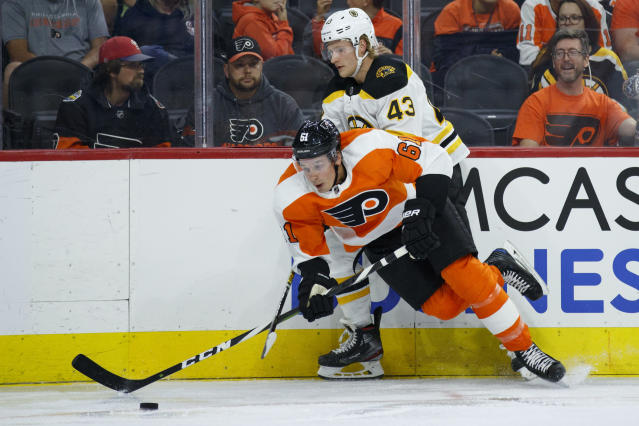 Philadelphia Flyers' Justin Braun (61) and Boston Bruins' Danton Heinen (43) compete for the puck during the third period of a preseason NHL hockey game, Thursday, Sept. 19, 2019, in Philadelphia. (AP Photo/Matt Slocum)