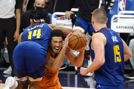Phoenix Suns guard Devin Booker draws a foul from Denver Nuggets guard Gary Harris (14) during the second half of an NBA basketball game Friday, Jan. 22, 2021, in Phoenix. (AP Photo/Rick Scuteri)