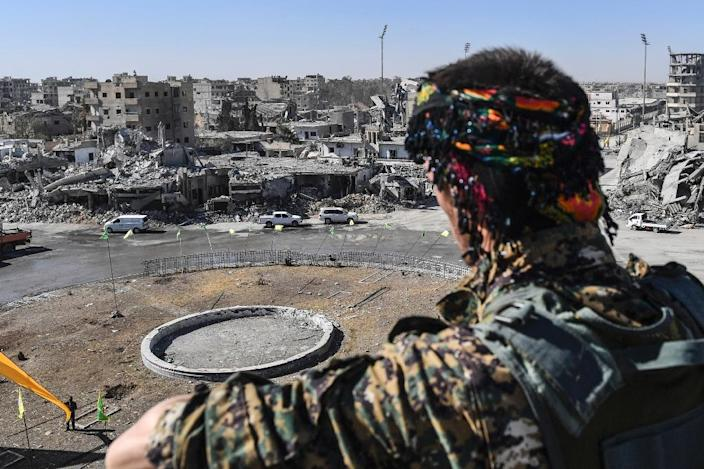 A fighter of the US-backed Syrian Democratic Forces watches over Raqa's Al-Naim square, where the Islamic State group once displayed the severed heads of its enemies, on October 18, 2017, the day after the city's capture (AFP Photo/BULENT KILIC)